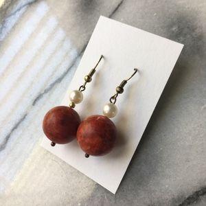 Red Stone ball earrings on gold hook earrings